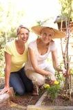 Hija mayor de la mujer y del adulto que se relaja en jardín Imagen de archivo