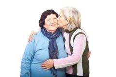 Hija mayor que besa a la madre mayor Imagen de archivo