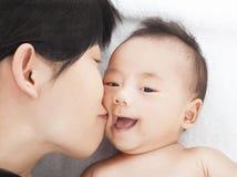 Hija o hijo asiática feliz del beso de la madre Imágenes de archivo libres de regalías