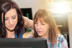 Hija que ayuda a su madre a trabajar en el ordenador, efecto luminoso Foto de archivo libre de regalías