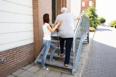 Hija que ayuda a su padre Climbing Staircase foto de archivo