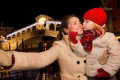 Hija que besa a la madre que toma el selfie en la Navidad Venecia, Italia Imagen de archivo libre de regalías