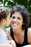 Hija que besa a su madre sonriente Imagenes de archivo