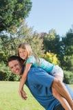 Hija que consigue a cuestas del papá que sonríe en la cámara Foto de archivo libre de regalías
