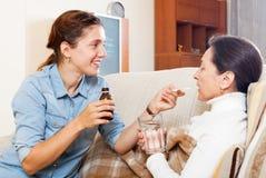 Hija que da el medicamento líquido a la mujer madura foto de archivo libre de regalías