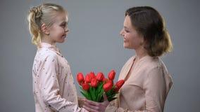 Hija que da las flores para mimar, enhorabuena del día de las mujeres, regalo de la sorpresa almacen de video
