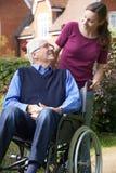 Hija que empuja al padre mayor In Wheelchair Fotografía de archivo