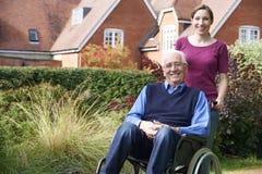 Hija que empuja al padre mayor In Wheelchair Fotografía de archivo libre de regalías