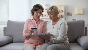 Hija que enseña a la tableta madura del uso de la madre, número de tarjeta que mecanografía, actividades bancarias en línea almacen de metraje de vídeo