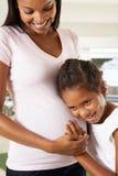 Hija que escucha el estómago de la madre embarazada imágenes de archivo libres de regalías