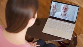 Hija que estudia en el extranjero tener charla video vía llamada del app del mensajero en el ordenador portátil con su padre mayo almacen de video