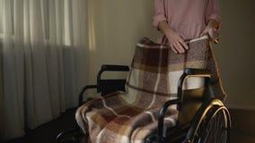 Hija que frota ligeramente la silla de ruedas vacía con el dolor, recordando a la madre desaparecida almacen de metraje de vídeo