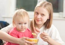 Hija que introduce de la madre con las gachas de avena Fotos de archivo