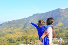 Hija que lleva de la madre asiática de la vista posterior en balcón en la ladera y el señalamiento de eso de ver imagen de archivo
