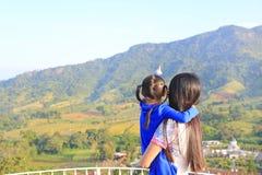 Hija que lleva de la madre asiática de la vista posterior en balcón en la ladera y el señalamiento de eso de ver imagenes de archivo