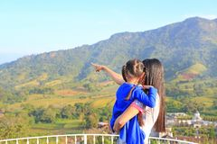 Hija que lleva de la madre asiática de la vista posterior en balcón en la ladera y el señalamiento de eso de ver fotos de archivo libres de regalías