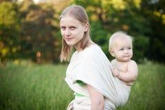 Hija que lleva de la madre en honda en campo Imagen de archivo libre de regalías
