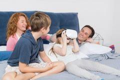 Hija que lleva los vidrios de Digitaces de la realidad virtual que se sientan con los padres y Brother On Bed, familia que se div Imagen de archivo libre de regalías