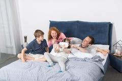 Hija que lleva los vidrios de Digitaces de la realidad virtual que se sientan con los padres y Brother On Bed, familia que se div Fotografía de archivo