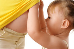 Hija que mira el vientre de la madre embarazada Fotos de archivo
