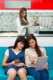 Hija que mira a la madre blanca del smartphone que cocina en cocina Foto de archivo libre de regalías