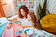Hija que mira las fotos que se sientan cerca de la madre que diseña la ropa foto de archivo libre de regalías