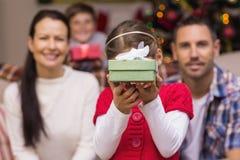 Hija que muestra un regalo con su familia detrás Fotos de archivo