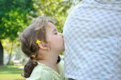 Hija que se besa el vientre embarazada de los mother's Imágenes de archivo libres de regalías