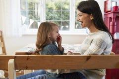 Hija que se sienta en el ` s Lap At Home And Laughing de la madre Imagenes de archivo