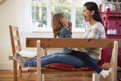Hija que se sienta en el ` s Lap At Home And Laughing de la madre Imagen de archivo