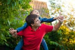 Hija que se sienta en hombros de los padres y que juega con él Foto de archivo libre de regalías