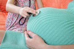 Hija que usa el blanco del estetoscopio que examina a la madre embarazada Imagen de archivo