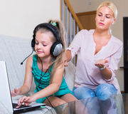 Hija que usa el ordenador portátil en vez de estudiar Fotografía de archivo libre de regalías