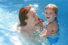 Hija rubia con la madre del redhead en piscina Fotos de archivo