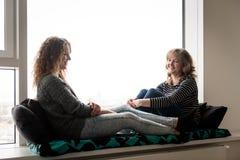 Hija sonriente en la conversación con su madre Fotografía de archivo