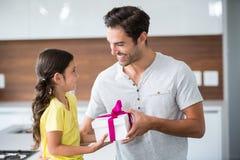 Hija sonriente que da la caja de regalo al padre Foto de archivo libre de regalías