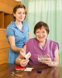 Hija sonriente que pide el dinero envejecido de la madre Imagen de archivo libre de regalías