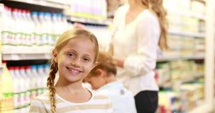 Hija sonriente que sostiene la leche y que hace los pulgares para arriba almacen de metraje de vídeo