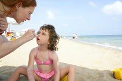 Hija y madre en la humedad de la pantalla de sol de la playa Fotografía de archivo