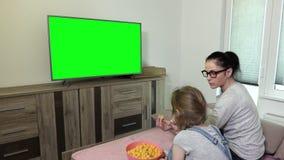 Hija y madre que comen las patatas a la inglesa del cuenco y usar teledirigido cerca de la TV con la pantalla verde almacen de video