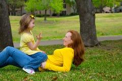 Hija y madre que juegan contando la mentira en césped Foto de archivo