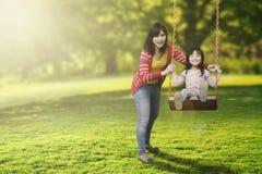 Hija y madre que juegan el oscilación Imagen de archivo libre de regalías