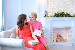 Hija y madre que se sientan junto en el sofá, sonriendo a cada o Fotos de archivo