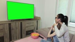 Hija y madre que ven la TV con la pantalla verde metrajes