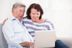Hija y padre que ríen mientras que usa el ordenador portátil Imagen de archivo