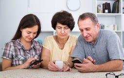 Hija y sus padres maduros que se sientan con los teléfonos en casa fotos de archivo