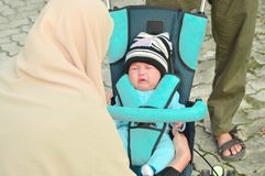Hijab母亲小心在有她的丈夫的公园她哭泣的婴孩 免版税库存图片