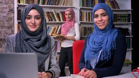 hijab回教女孩的令人愉快的面孔坐在图书馆里在膝上型计算机附近和看与兴高采烈的面孔的照相机,现代 股票视频