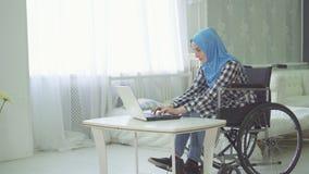 hijab废人的女孩使用膝上型计算机的一个轮椅的 库存图片