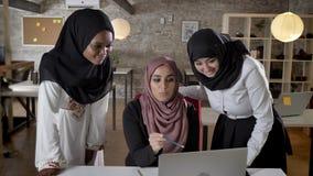hijab的三名年轻回教妇女的谈论项目和微笑,指向在膝上型计算机的,谈论经营计划  股票录像